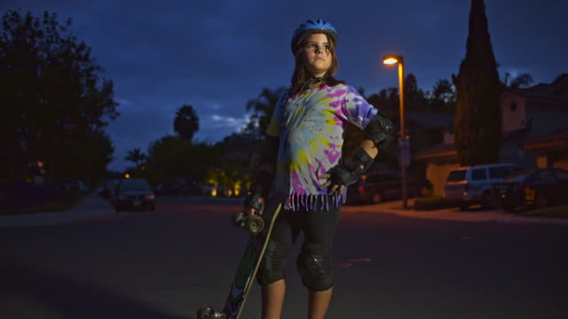 10 year old skater girl with skateboard on neighborhood street at dusk. wide to med push in, jib. - elbow pad stock videos & royalty-free footage
