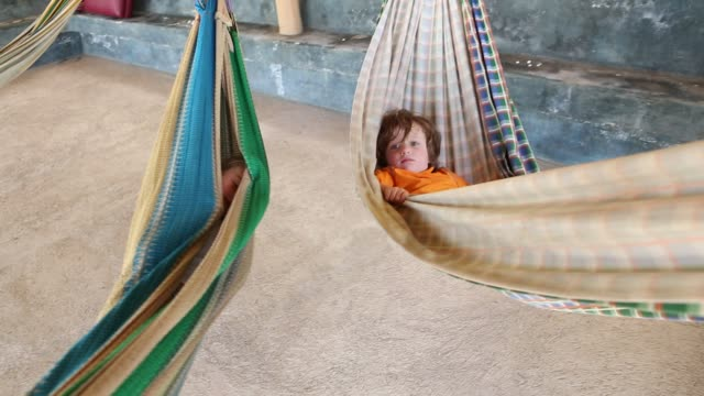 vidéos et rushes de 2 year old toddler boy and friend on a hammock - soeur