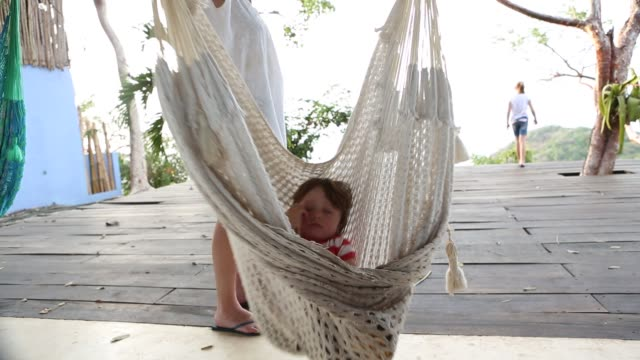 2 year old toddler boy and friend on a hammock - terrazza in legno video stock e b–roll