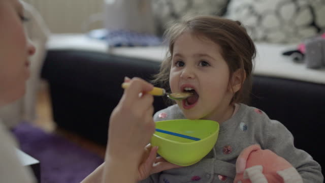 3 year old toddler girl eating soup - nutrire video stock e b–roll