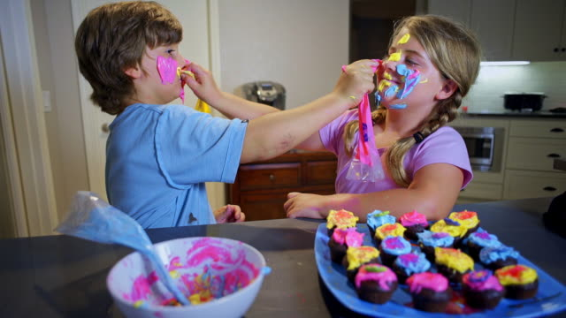 vídeos y material grabado en eventos de stock de 8 year old twins applying cupcake camouflage on their faces. - pastel intensidad del color