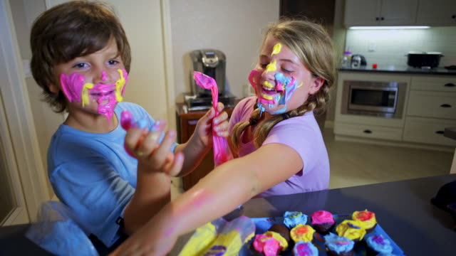 8 year old twins love how their faces look covered in cupcake frosting. - schmutzig stock-videos und b-roll-filmmaterial