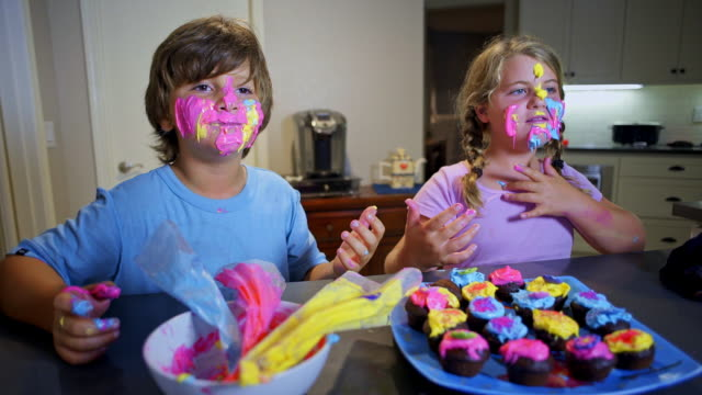 8 year old twins with frosting faces eat cupcakes