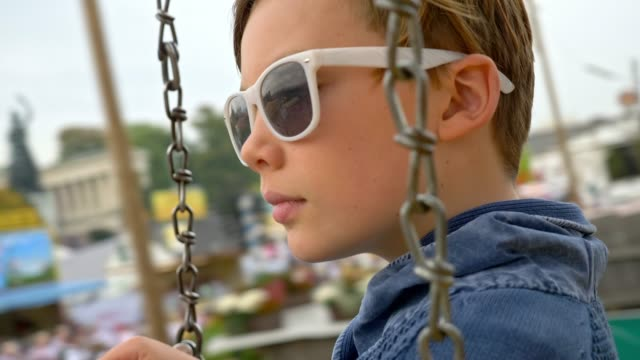 "10 year old with white sunglasses boy takes a chain swing carousel ride while visiting the ""Oide Wiesn"" during Oktoberfest 2017 - close up"