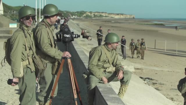 vídeos de stock, filmes e b-roll de 75 years after allied troops landed on the beaches of normandy to push nazi forces out of france men gather in vintage military uniforms on omaha... - uniforme militar