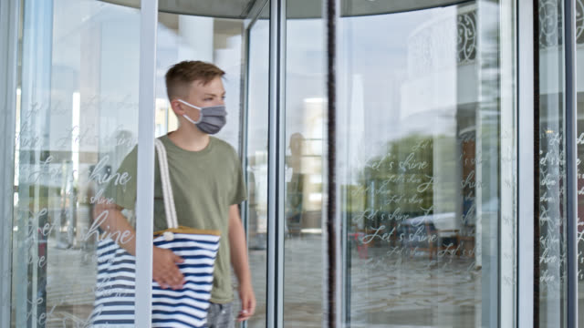 12 years old adolescent boy with corona mouth nose protection mask leaves hotel building - 12 13 years stock-videos und b-roll-filmmaterial