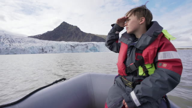 10 years old boy enjoys a rubber boat trip on fjallsárlón glacier lake in iceland - 10 11 years stock videos & royalty-free footage