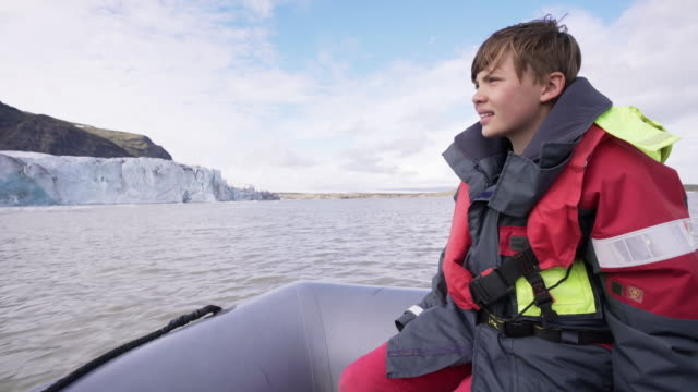 10 years old boy enjoys a rubber boat trip on fjallsárlón glacier lake in iceland - pre adolescent child stock videos & royalty-free footage