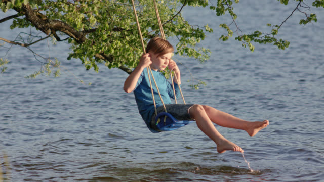 vídeos de stock, filmes e b-roll de 9 years old boy in jeans shorts and blue shirt sits on a swing mounted on a tree hanging over water lakesides by the beach of lake staffelsee and is enjoying himself on a sunny summer day / shot from buchau camping island - 10 11 years