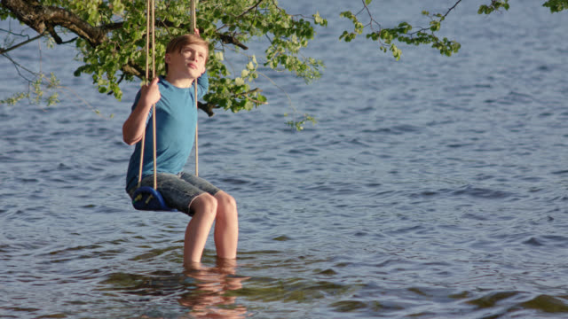 9 years old boy in jeans shorts and blue shirt sits on a swing mounted on a tree hanging over water lakesides by the beach of lake staffelsee and is enjoying himself on a sunny summer day / shot from buchau camping island - shorts stock-videos und b-roll-filmmaterial