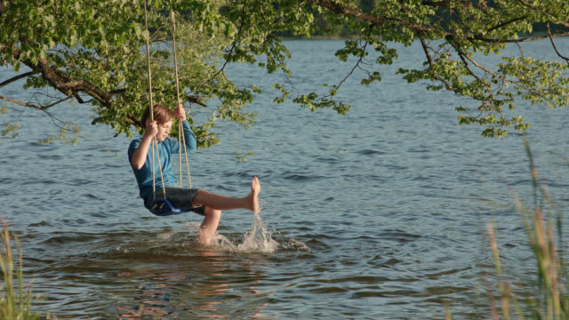 vídeos de stock e filmes b-roll de 9 years old boy in jeans shorts and blue shirt sits on a swing mounted on a tree hanging over water lakesides by the beach of lake staffelsee and is bored of digital detox while splashing with his feet in the water on a sunny summer day - descalço
