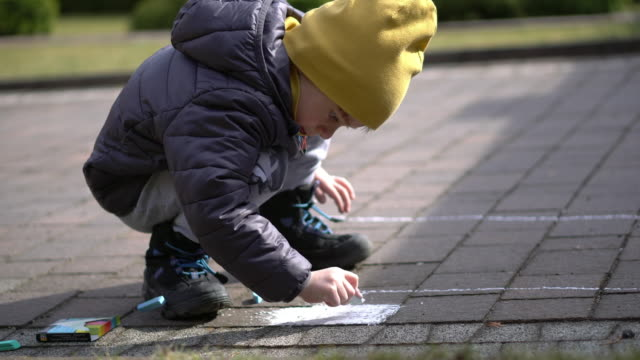 5 years old boy is drawing with colored chalk on the cobblestones in front of the house - gessetto da lavagna video stock e b–roll