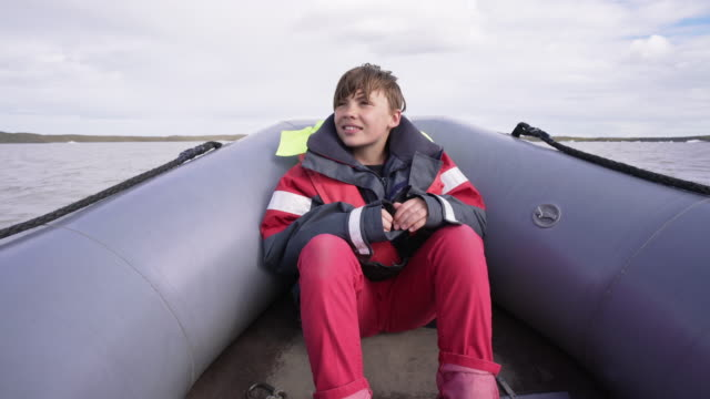 10 years old boy sits in a rubber boat on fjallsárlón glacier lake in iceland - 10 11 years stock videos & royalty-free footage