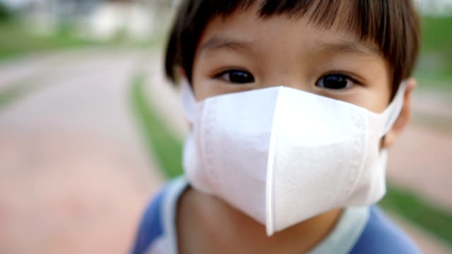 slo mo 3 years old boy wearing pollution masks and looking at camera. - pollution mask stock videos & royalty-free footage