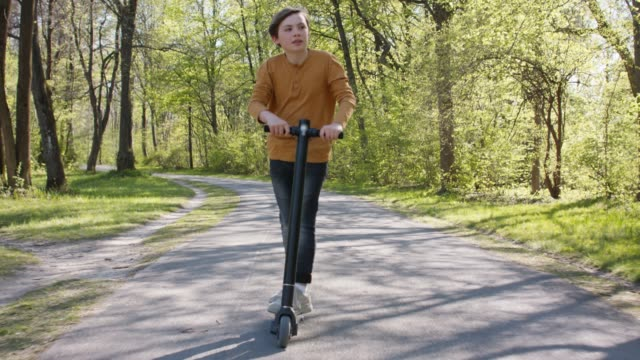 stockvideo's en b-roll-footage met 11 years old boy with blond hair and dark jeans enjoys a ride on his trendy black electric scooter in a park. - 10 11 jaar