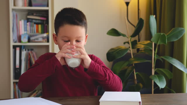 6-7 years old cute child drinking milk on table. he knows that he needs to drink milk for healthy bones. he loves milk. - 6 7 years stock videos & royalty-free footage