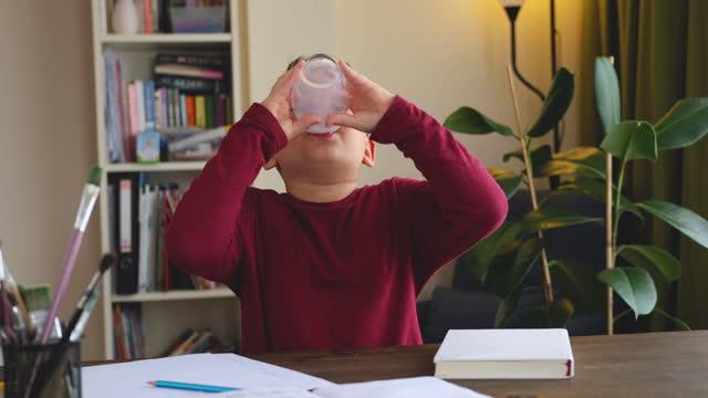 6-7 år gammal söt barndrickande mjölk på bordet. han vet att han behöver dricka mjölk för friska ben. han älskar mjölk. - 6 7 years bildbanksvideor och videomaterial från bakom kulisserna