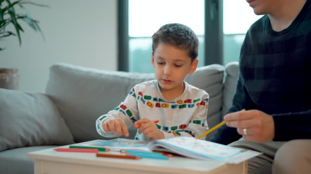 4-5 years old little boy doing homework, coloring pages whit his father - 4 5 years stock videos & royalty-free footage