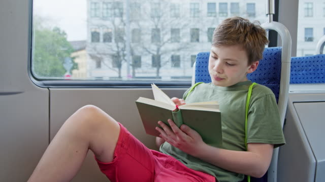 vidéos et rushes de 12 years old maverick schoolboy in tramway trambahn reading a analoge book while day on the move. - transports publics