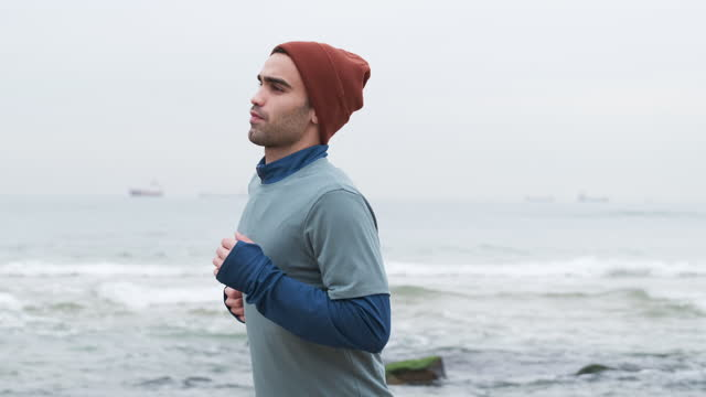 uomini di 20-24 anni che corrono sulla costa a temperatura fredda - 20 24 years video stock e b–roll