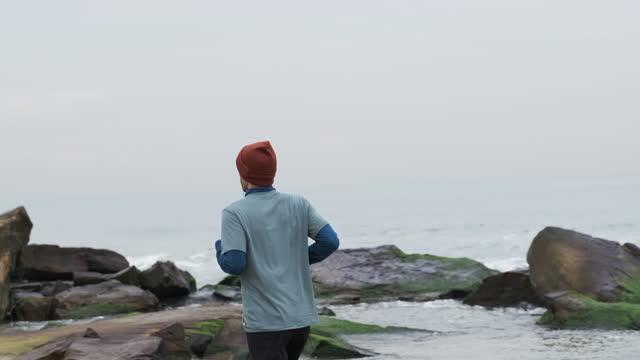 20-24 jahre alte männer laufen an der küste auf kaltem temperatur - 20 24 years stock-videos und b-roll-filmmaterial
