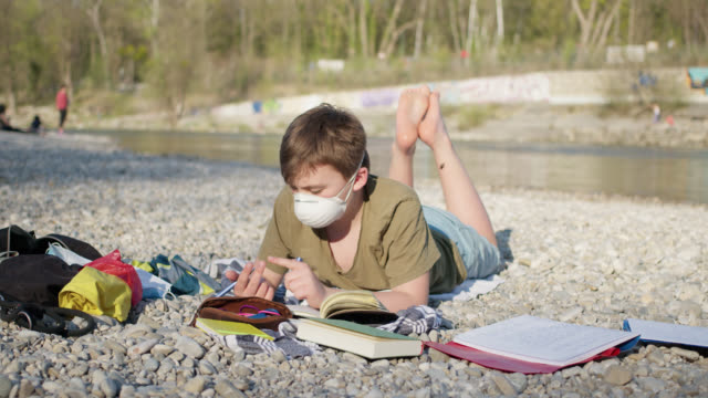 12 years old schoolboy wearing ffp2 protective mask doing homework outside while sunny day. - 12 13 years stock-videos und b-roll-filmmaterial