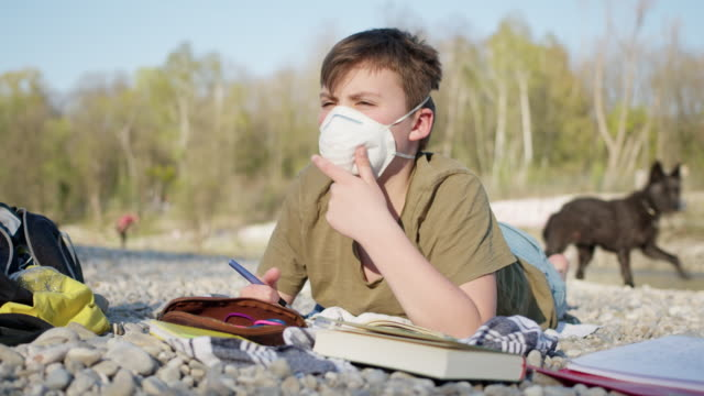 12 years old schoolboy wearing ffp2 protective mask with his dog in background doing boring homework outside while sunny day. - 12 13 years stock-videos und b-roll-filmmaterial