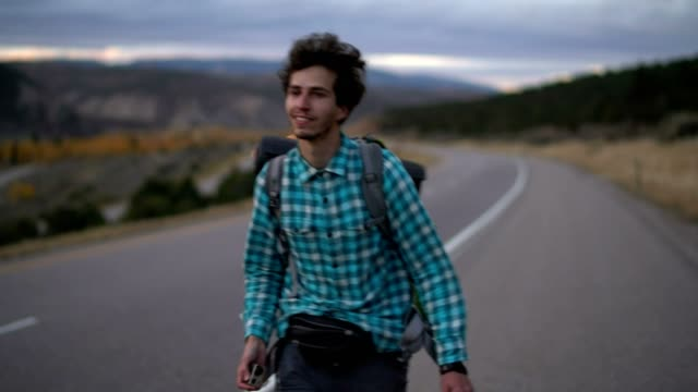 30 years old young man, traveler, walking with the backpack on the highway in mountain in colorado, usa. - explorer stock videos and b-roll footage