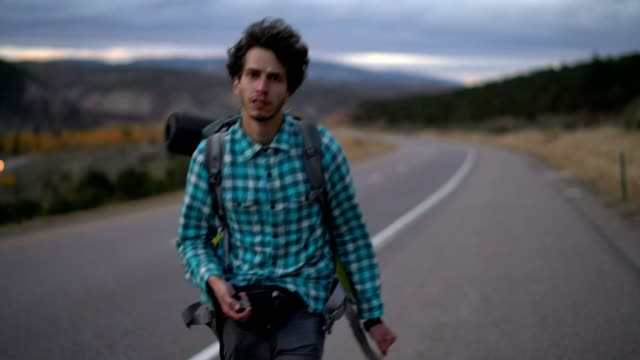 30 years old young man, traveler, walking with the backpack on the highway in mountain in Colorado, USA.