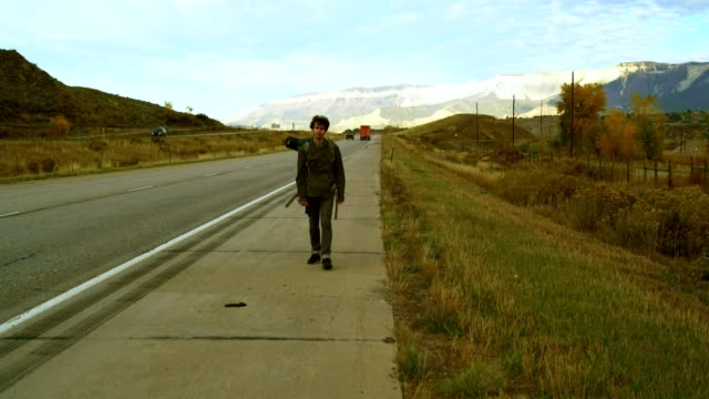 30 years old young man, traveler, walking with the backpack on the highway in mountain in colorado, usa. - 30 34 years video stock e b–roll