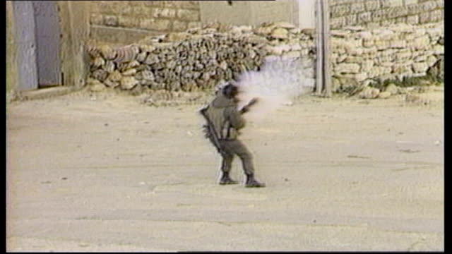 vídeos de stock e filmes b-roll de story 1 west bank palestinians rioting and throwing stones as palestine flags flying israeli soldier runs along and fires tear gas canister israeli... - palestino