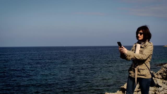 40 Jahre Frau im Urlaub mit Handy zum Fotografieren