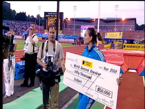 Yelena Isinbayeva at photo call holding up large cardboard cheque for breaking the Women's Pole Vault World Record 2004 Crystal Palace Athletics...