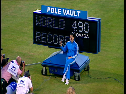 Yelena Isinbayeva poses on electronic display board featuring World Record height jumped surrounded by paparazzi Women's Pole Vault 2004 Crystal...