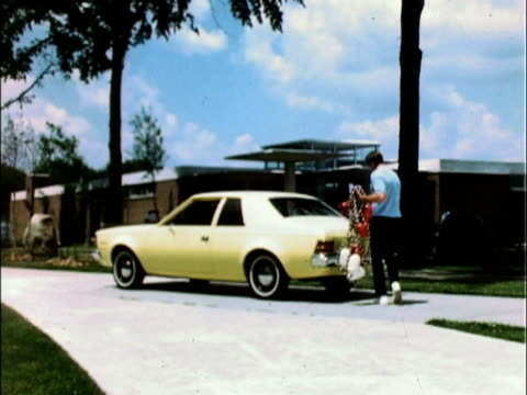 vídeos y material grabado en eventos de stock de yellow amc hornet parked outside building; man with swimming pool ropes and buoys walks toward car; opens trunk / man in driver's seat; fastens seat... - 1971