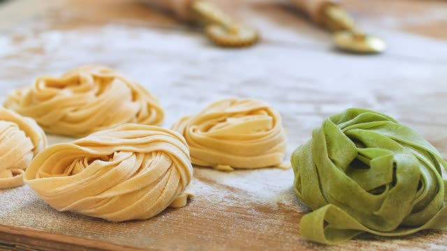 yellow and green pasta ribbons on wooden board - tagliatelle stock videos and b-roll footage