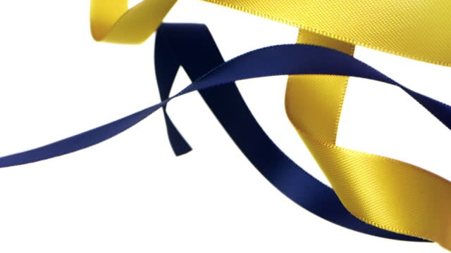 yellow and navy blue colored ribbons on white background, for celebration events and party for new year, birthday party, christmas or any holidays, waiving and curling in super slow motion and close up - banner sign stock videos & royalty-free footage