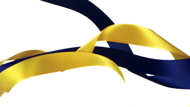 yellow and navy blue colored ribbons on white background, for celebration events and party for new year, birthday party, christmas or any holidays, waiving and curling in super slow motion and close up - banner stock videos & royalty-free footage