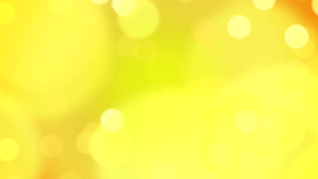 yellow and orange particles floating in slow motion. loopable footage. - yellow background stock videos & royalty-free footage