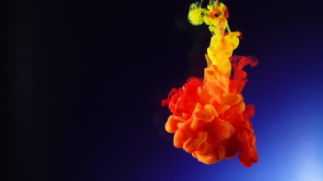 水の青の背景に落ちる黄色と赤のインクドロップ - 黄色点の映像素材/bロール