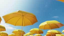 Yellow beach umbrellas on a background of blue sky