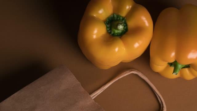 紙の買い物袋の黄色ピーマン - 茶色背景点の映像素材/bロール