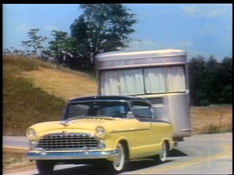 stockvideo's en b-roll-footage met 1955 yellow + black hudson pulling trailer motor home around curve on country road - 1955