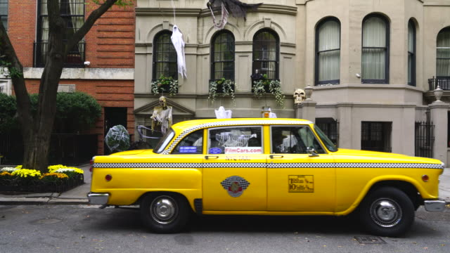 Yellow Cab is leaving residence decorated by Halloween decoration at Upper East Manhattan New York on Oct 29 2016