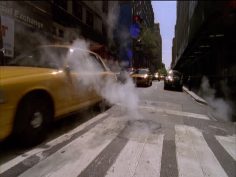 Yellow Cabs and Cars Passing Over a Pedestrian Crossing and Steam Rising From a Manhole on 5th Avenue and 35th Street, New York, USA