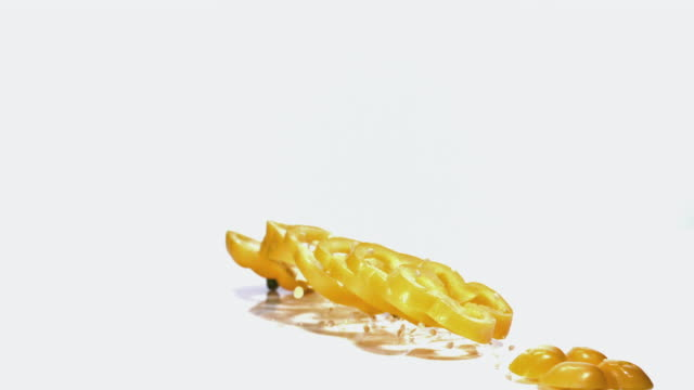 ms slo mo yellow capsicum falling on floor against white background / vieux pont, normandy, france  - bell pepper stock videos & royalty-free footage