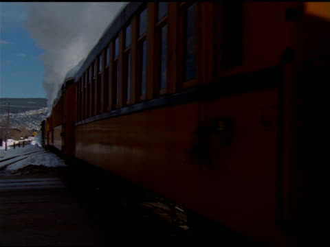 yellow carriages of passenger train travel past camera, conductor on back of train waves hat, durango - transport conductor stock videos & royalty-free footage