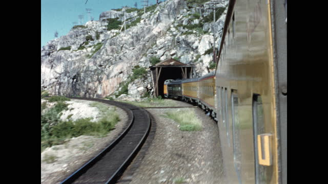 yellow cars of passenger train disappear into tunnel through granite mountain - californian sierra nevada stock videos & royalty-free footage