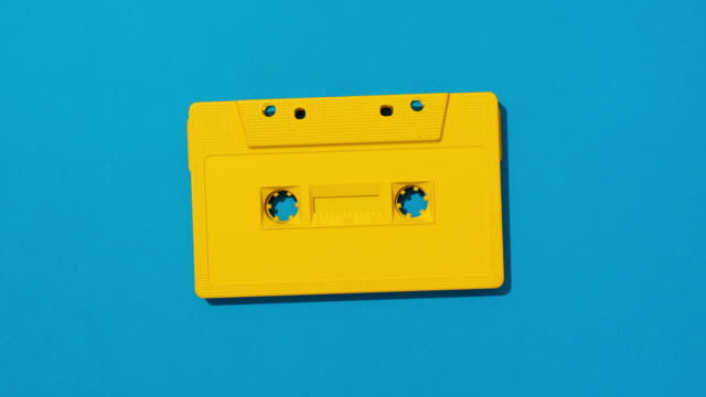 vídeos de stock e filmes b-roll de yellow cassette tape turning on blue background - fora de moda estilo