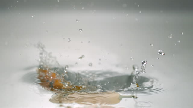 cu slo mo yellow chili peppers falling into water / new jersey, usa - cinque oggetti video stock e b–roll